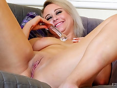 Mature blue eyed blonde MILF Elle masturbates bent over on the couch