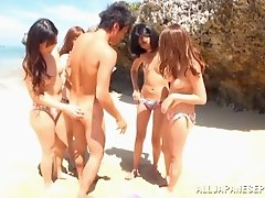A group of Japanese girls in bikinis get fucked at the beach