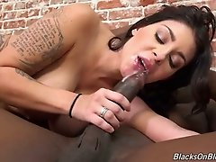 Tattooed raven haired bitch with fake boobs blows giant black dick