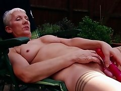 Granny in lingerie and stockings masturbates in the garden